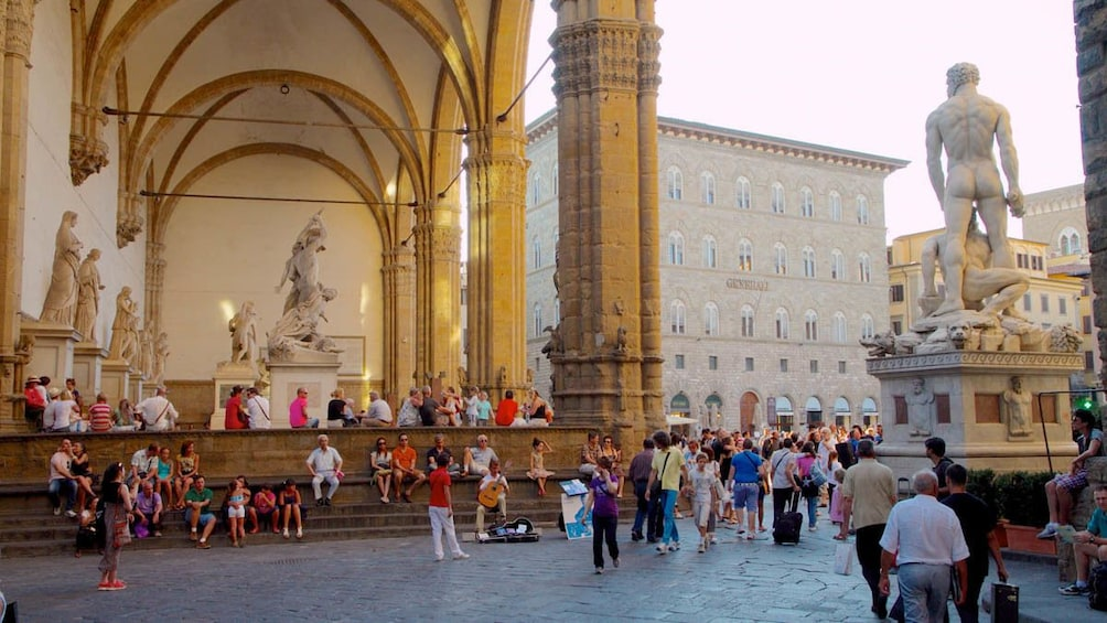 Courtyard view of Uffizi gallery with several visitors.