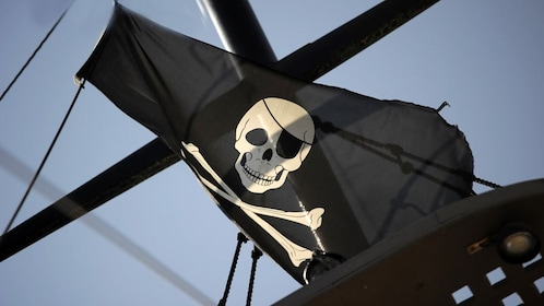 A Pirate flag blowing in the wind on a ship