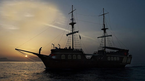 A silhouetted Pirate ship on the Greek coastline at dusk.