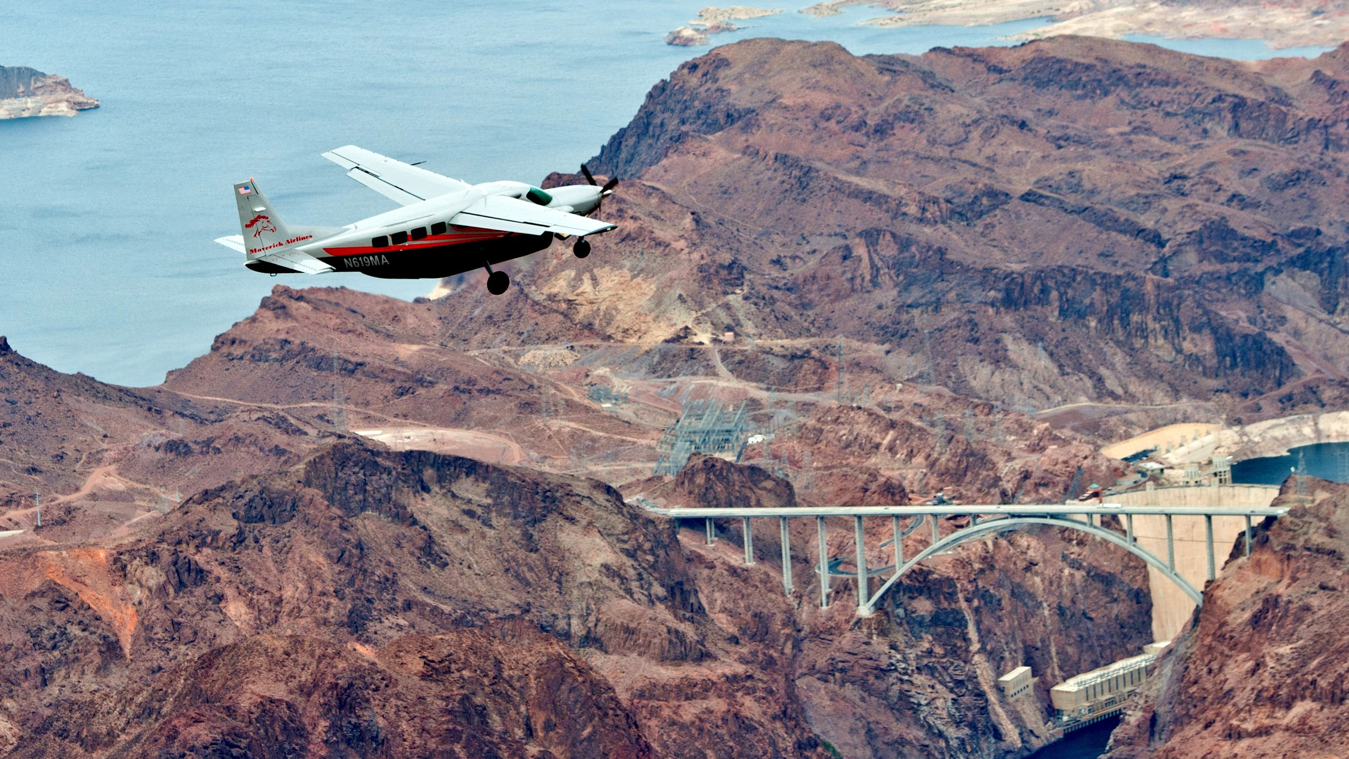 A plane flies over the Grand Canyon, Colorado River, a bridge and the Hoover Dam