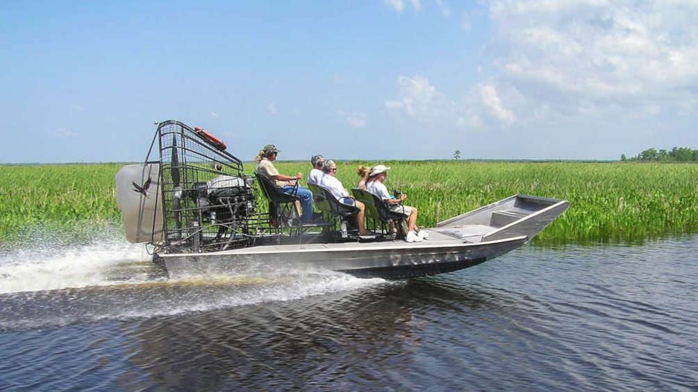 Show item 1 of 9. AIrboat shown riding through bayou.
