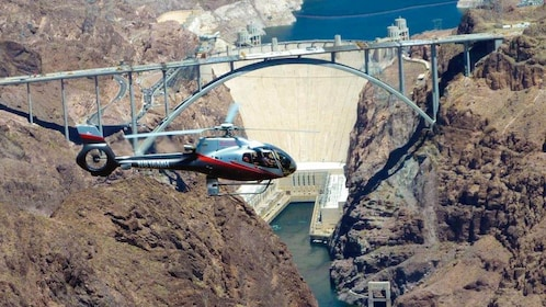 Helicopter shown flying over Hoover Dam.