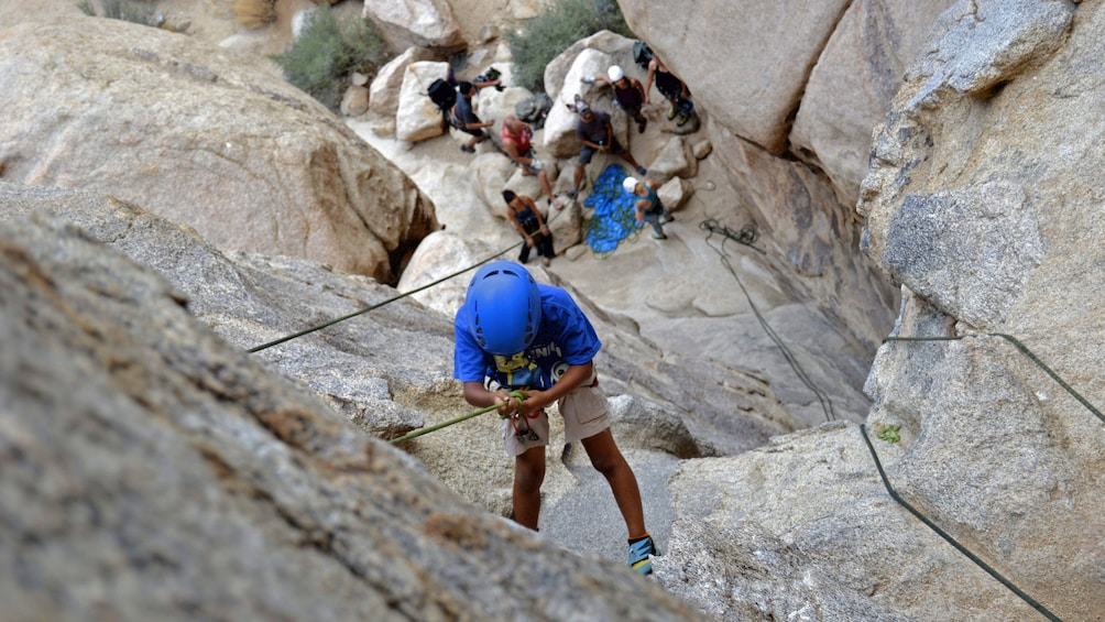 Show item 2 of 5. Rock climber repelling down rock face in Palm Springs