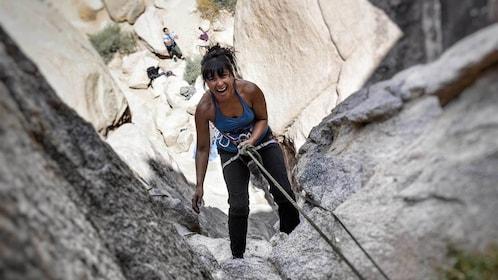 Woman enjoying climb up rock face in Ontario, California
