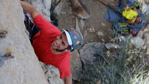 Man in a red shirt and helmet climbs a rock face