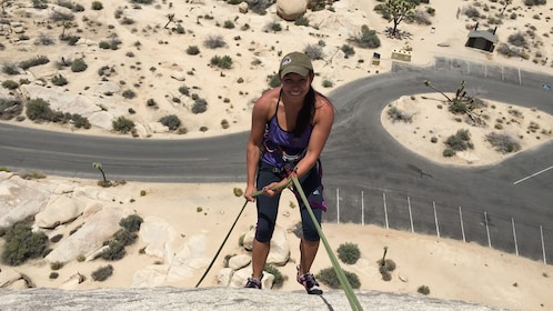 Woman looks up at the camera while rock climbing above a parking lot