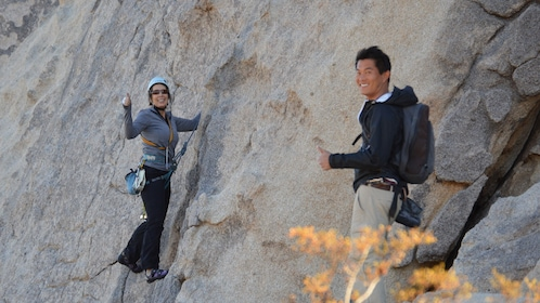 Two people give thumbs up while rock climbing