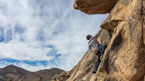 upward angle of a man climbing up a rock face