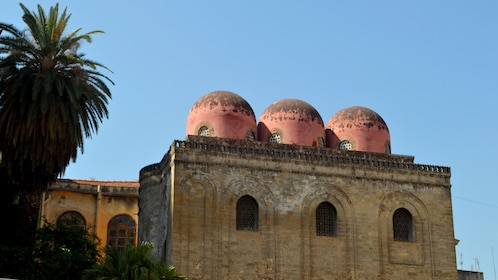 Three red domes on the roof of a church in Palermo