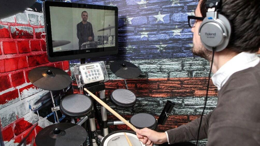 正在顯示第 3 張相片,共 6 張。 Man playing drum machine with video of Ringo Starr in Liverpool