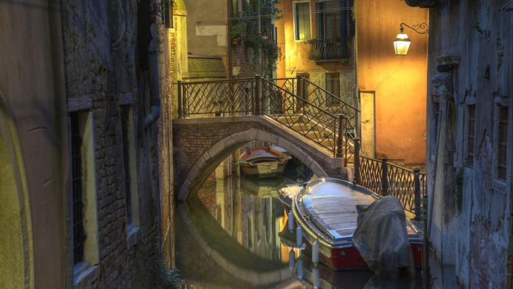 A back alley canal lit by street lamp in Venice at night.