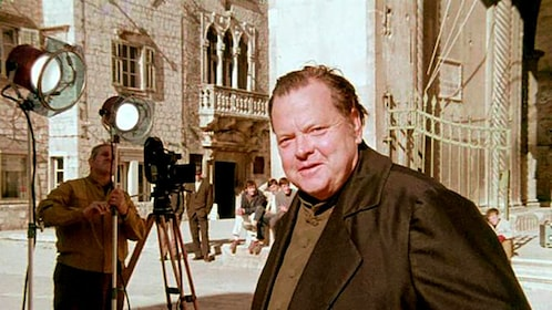 Orson Welles on location in Venice with movie equipment in the background