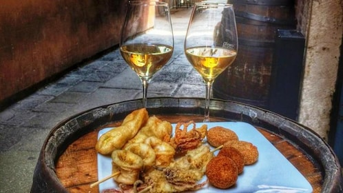 On top of a barrel sits two glasses of wine and a selection of fried appetizers