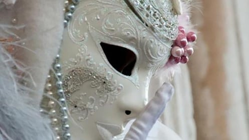 An Italian white masquerade mask wearing woman holds a finger to her mouth