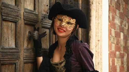 A woman in an Italian Masquerade costume leans up against an old wooden door