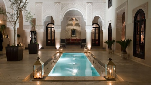 Morrocco, Fez, illuminated pool in courtyard, dusk
