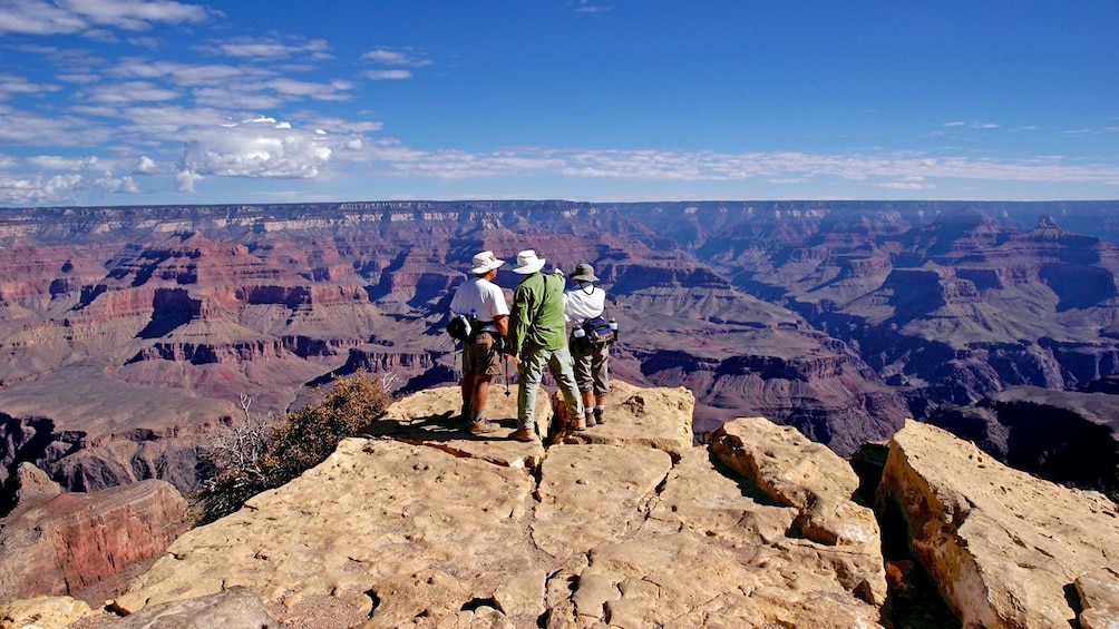 Show item 3 of 5. hikers standing on a cliff at Grand Canyon