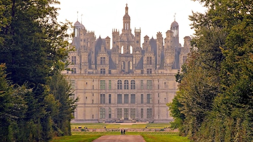 standing at the front of the Chateau de Chambord in France