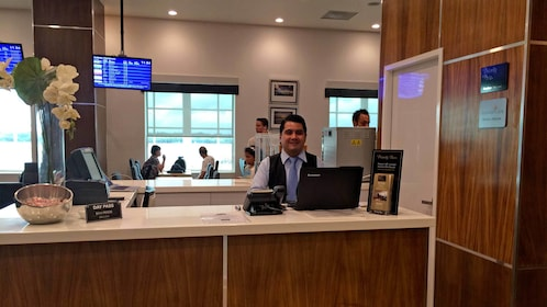 Receptionist inside the Mera Business Lounge at Cancun Airport in Mexico