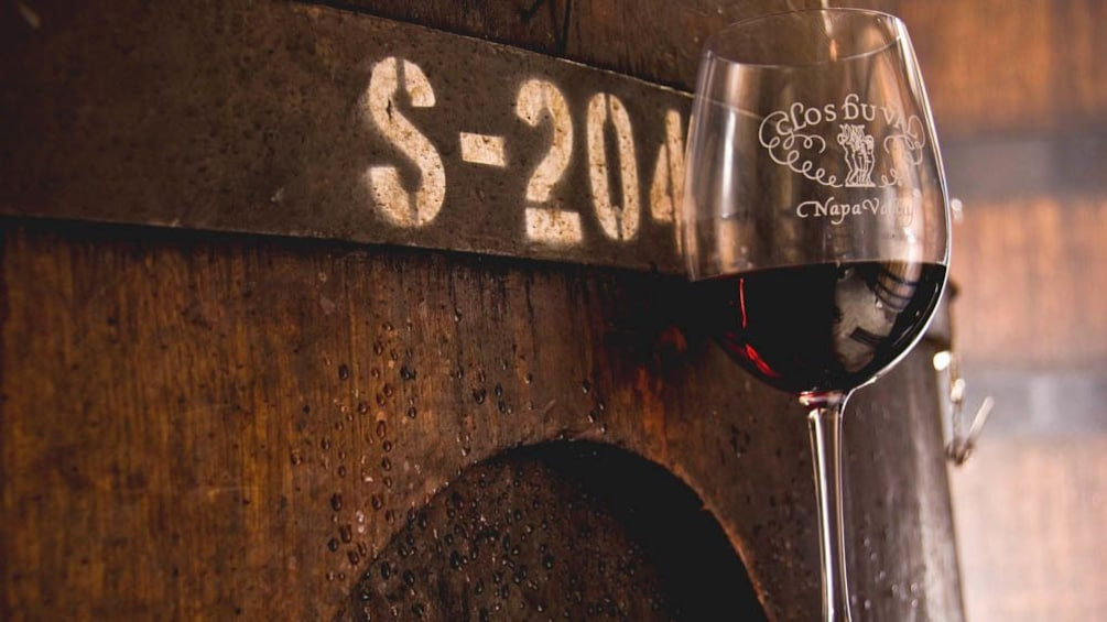 Close up of wine  glass against barrel of wine.