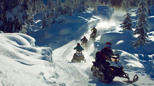 snowmobiles going down a hilly snow trail in Wistler