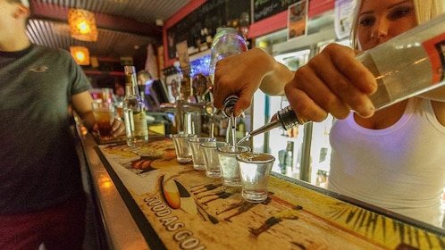 Interior view of bartender pouring shots.
