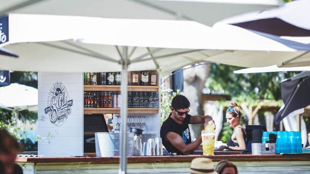Foto 4 van 5. View of bartender mixing drink at bar.