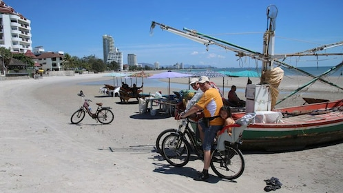 Bicyclists near boats on the beach in Hua Hin