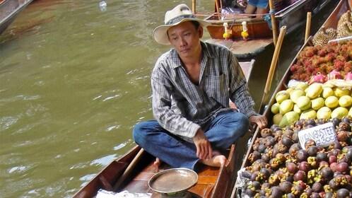 Man selling fruits at the floating market in Bangkok