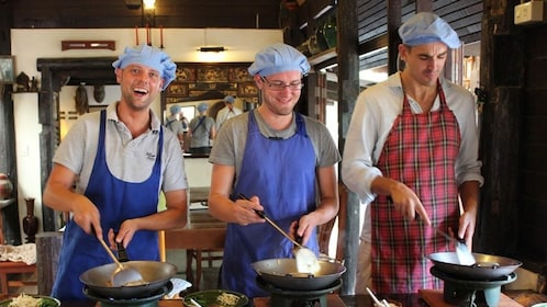 Three men cook in Thai Cooking Class at Hua Hin