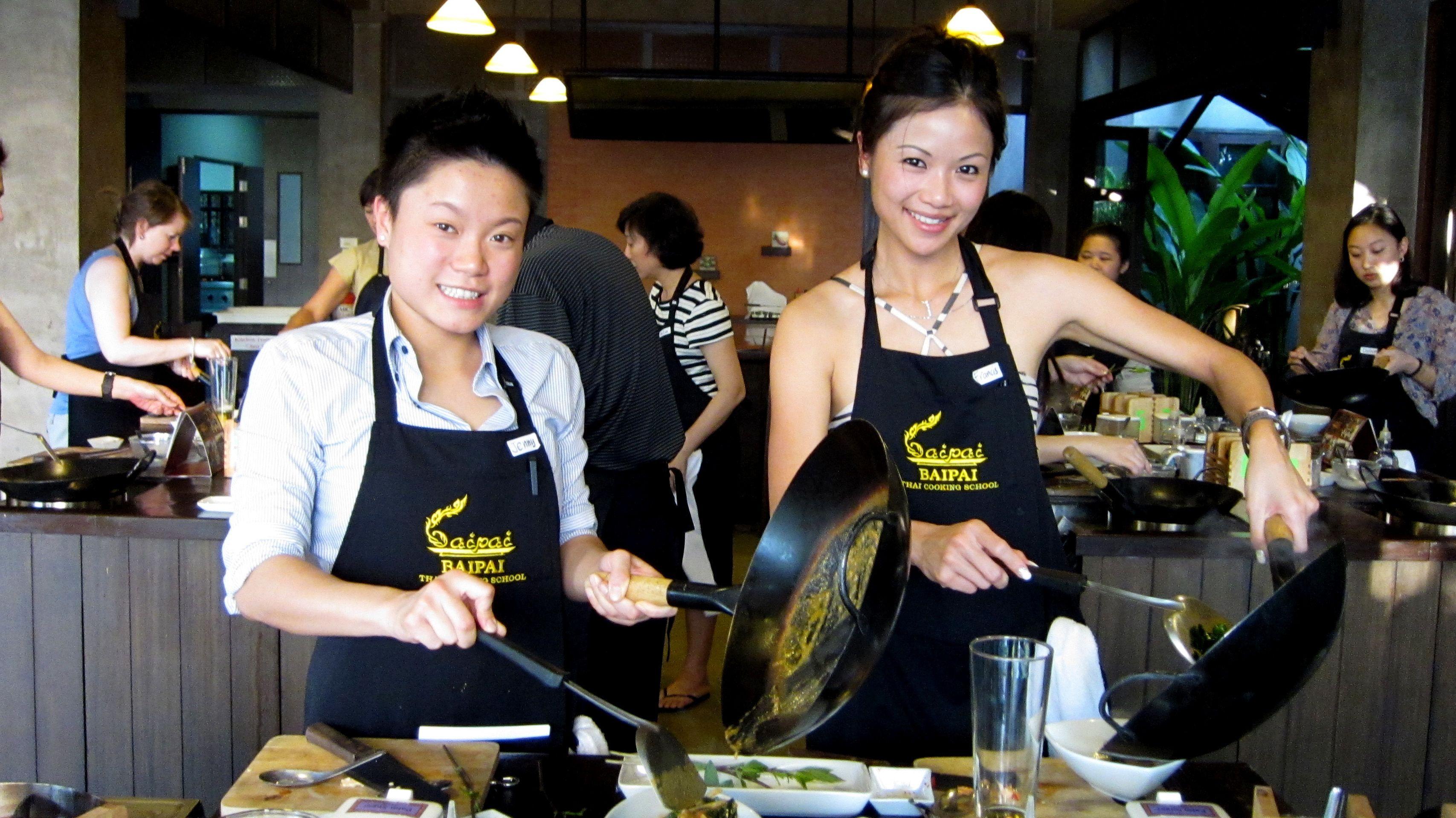 Two women cooking in Bai Pai Thai Cooking School at Bangkok