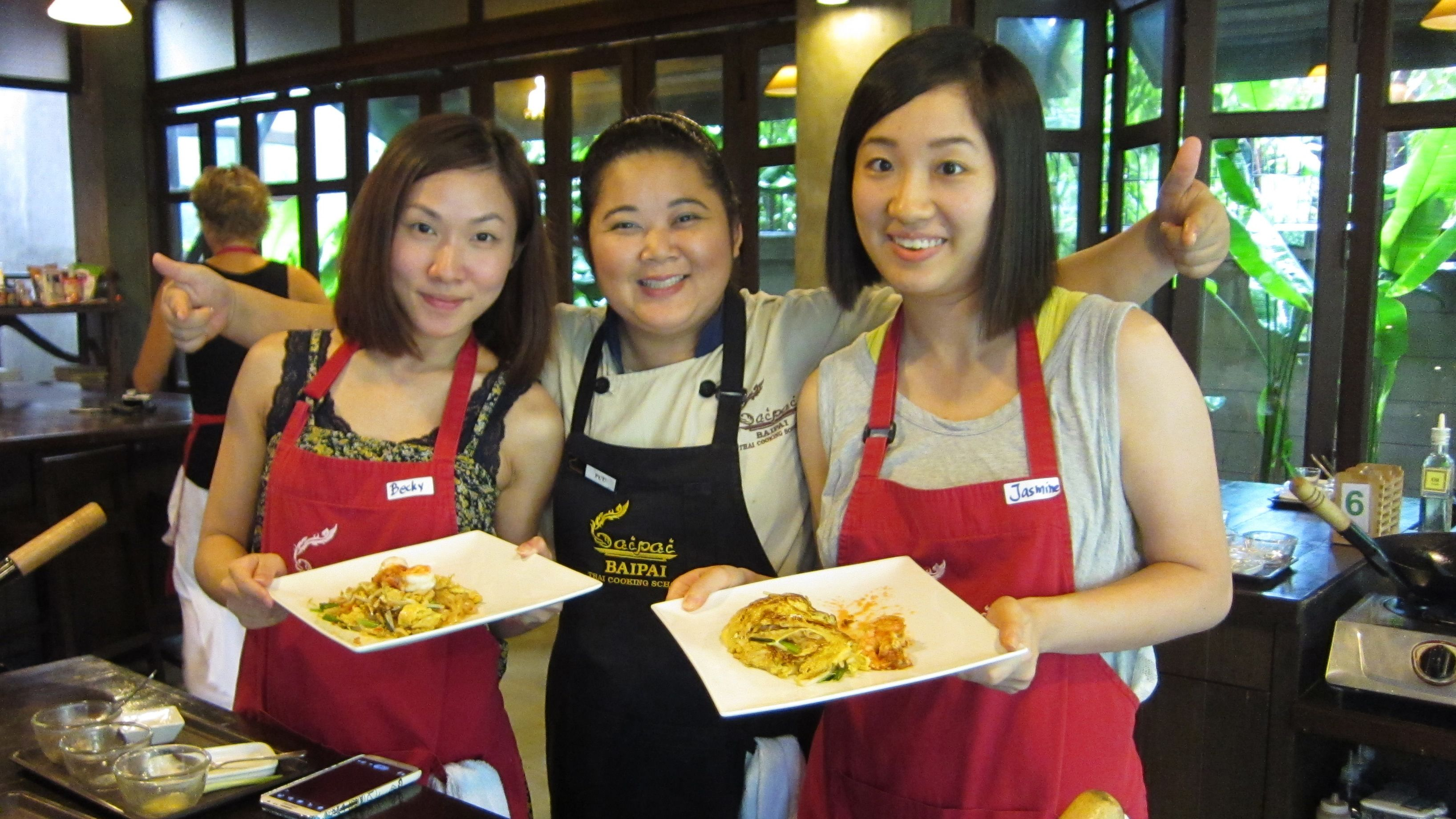 Three people hold up finished dishes in Bai Pai Thai Cooking School at Bangkok
