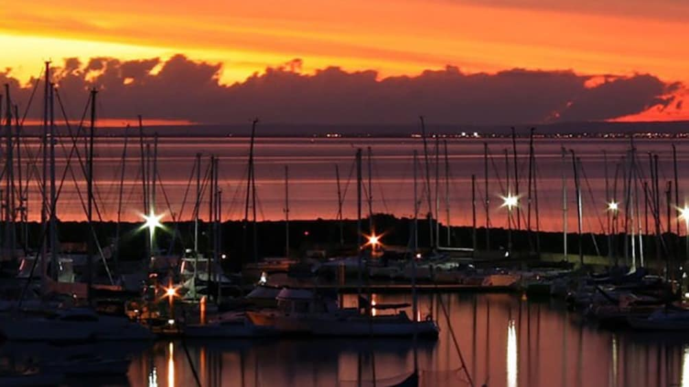 Show item 5 of 5. The sun sets behind clouds and docked boats on the coastline of South Carolina