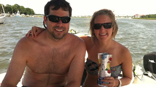 A woman in a bikini drinks wine from a bag next to a shirtless man on a boat.