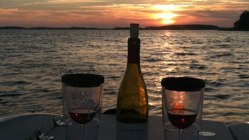 Two glasses of wine and a wine bottle on a boat as the sun sets on the water off South Carolina