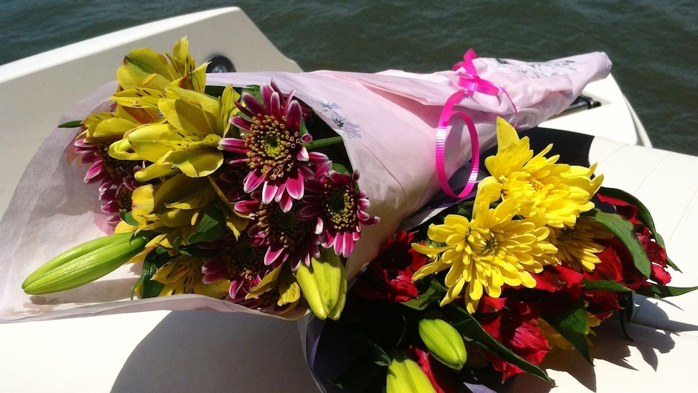 Show item 4 of 4. Two bouquets of flowers on a boat.