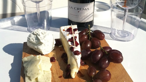 A wood platter of cheese, and grapes next to a bottle of wine and glasses on a boat