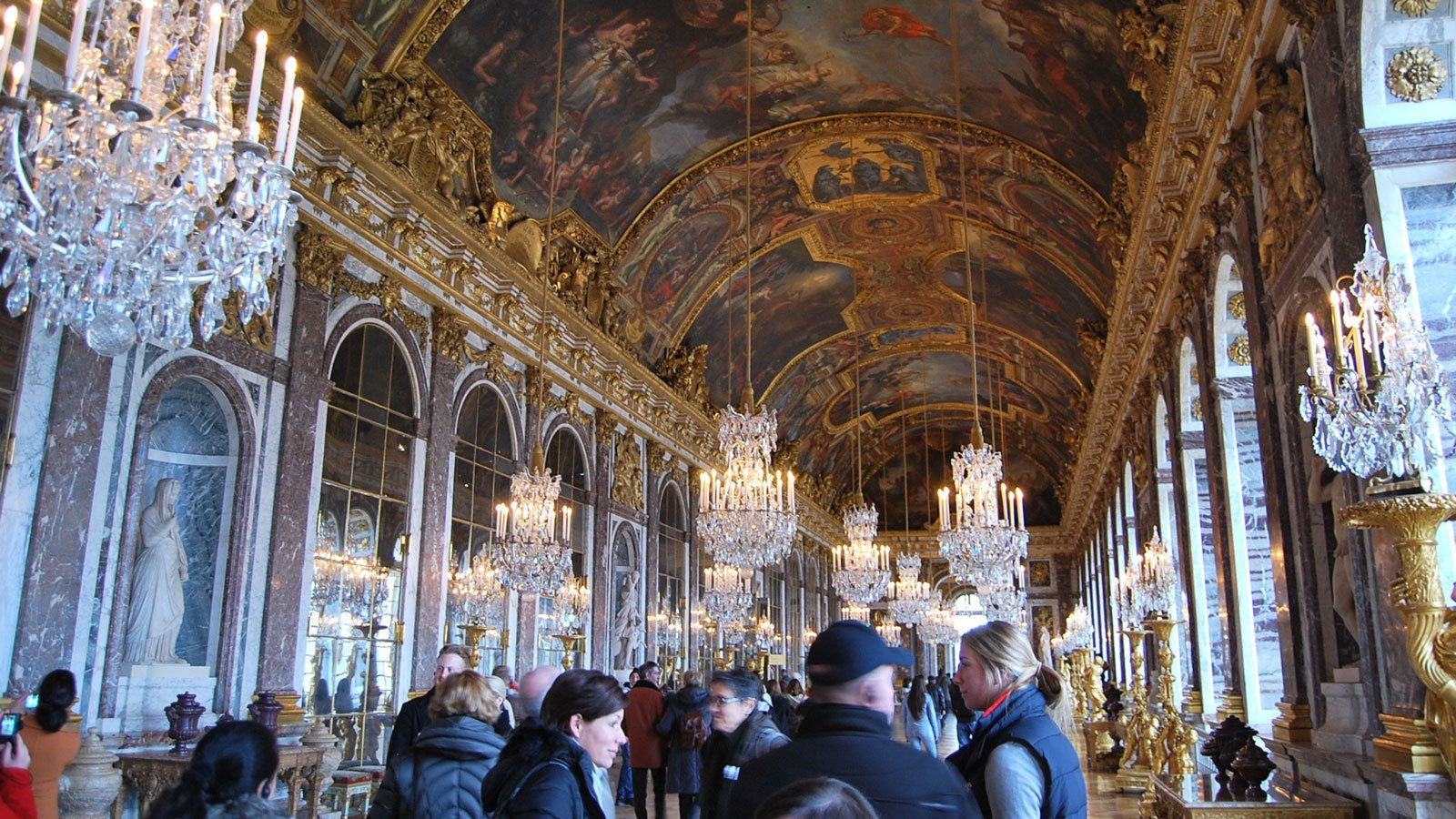 crowded hallways inside the Versailles Palace in France