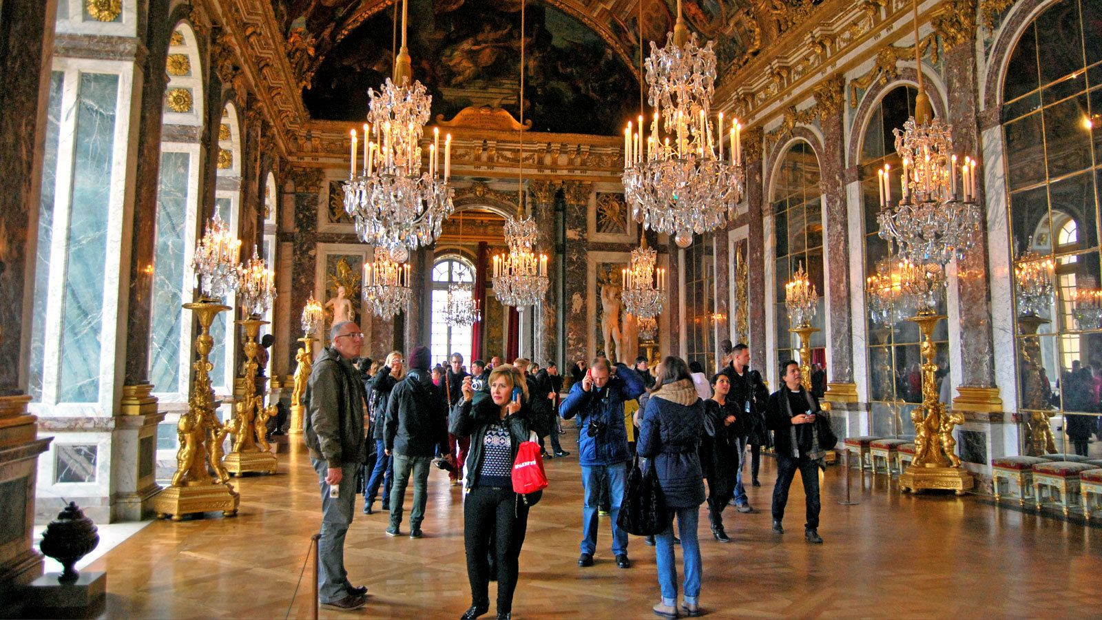 walking through the ornamented hallways inside the Versailles Palace in France