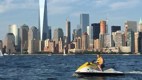 Man rides a Jet Ski past the island of Manhattan
