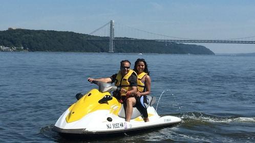 Two people on a Jet ski outside the Brooklyn Bridge