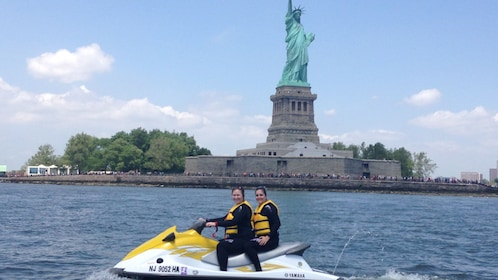 Two people on a Jet Ski ride past the Statue of Liberty