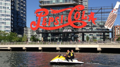 Man and woman ride a Jet Ski past a large Pepsi sign