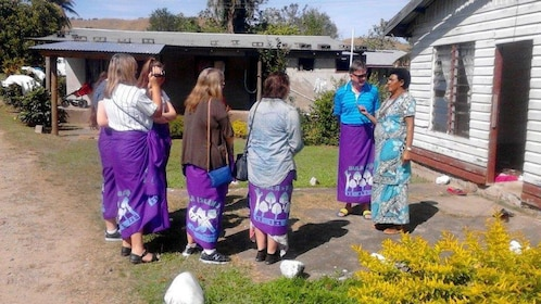 Guide with tour group wearing traditional skirts in Fiji