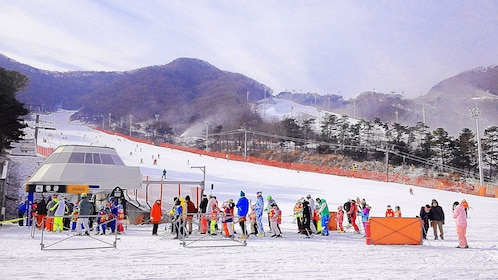 Group of skiers at the bottom of a gentle ski hill in South Korea