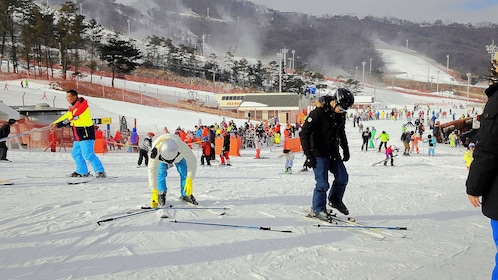 Skiers putting on skis in the snow in South Korea