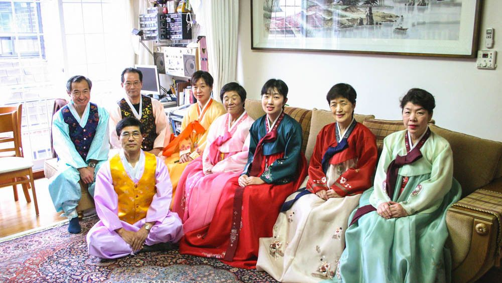 Several locals seated in living room wearing traditional clothing.