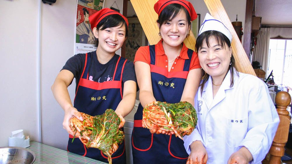 Women holding Kimchi posing for camera with cook.