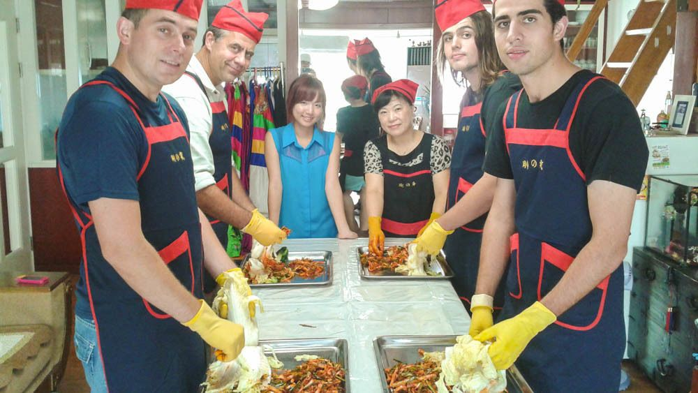 Several people show in a cooking class preparing kimchi.