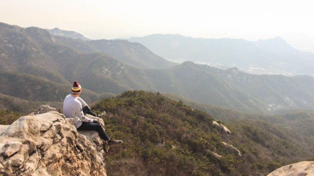 正在顯示第 1 張相片,共 5 張。 Hiker sitting on mountain peak observing the distance.